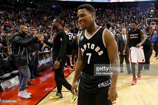 As Toronto Raptors guard Kyle Lowry walks off the court Drake says hello to the Heat's Dwyne Wade who did not play tonight Toronto Raptors vs Miami...