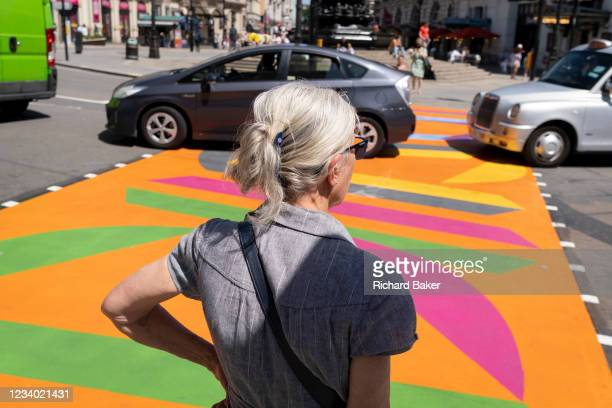 As traffic passes-by, a white-haired woman waits to cross the road, over the multi-coloured markings of a crossing at Piccadilly Circus, on 16th July...
