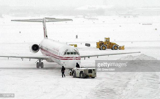 As Trans World Airlines workers back a TWA plane out for takeoff a front loader moves snow off of the runway December 13 2000 at LambertSt Louis...