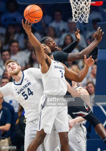 As Tre Scott of the Cincinnati Bearcats looks back Quentin Goodin of the Xavier Musketeers snags the rebound at Cintas Center on December 2 2017 in...
