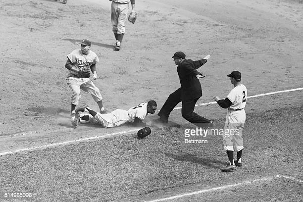 As umpire Stan Landes flashes the safe sign Giant outfielder Willie Mays sprawls across first base after sliding into the bag to beat out an infield...