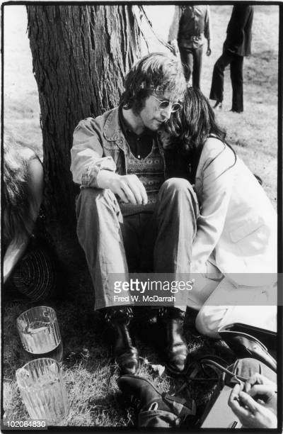 As unidentified others stand or sit nearby British musician John Lennon and his wife JapaneseAmerican artist and musician Yoko Ono sit on the grass...