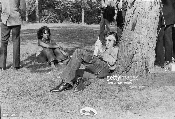 As unidentified others stand or sit nearby British musician John Lennon sits on the grass and leans against a tree with a paper airplane in his hand...