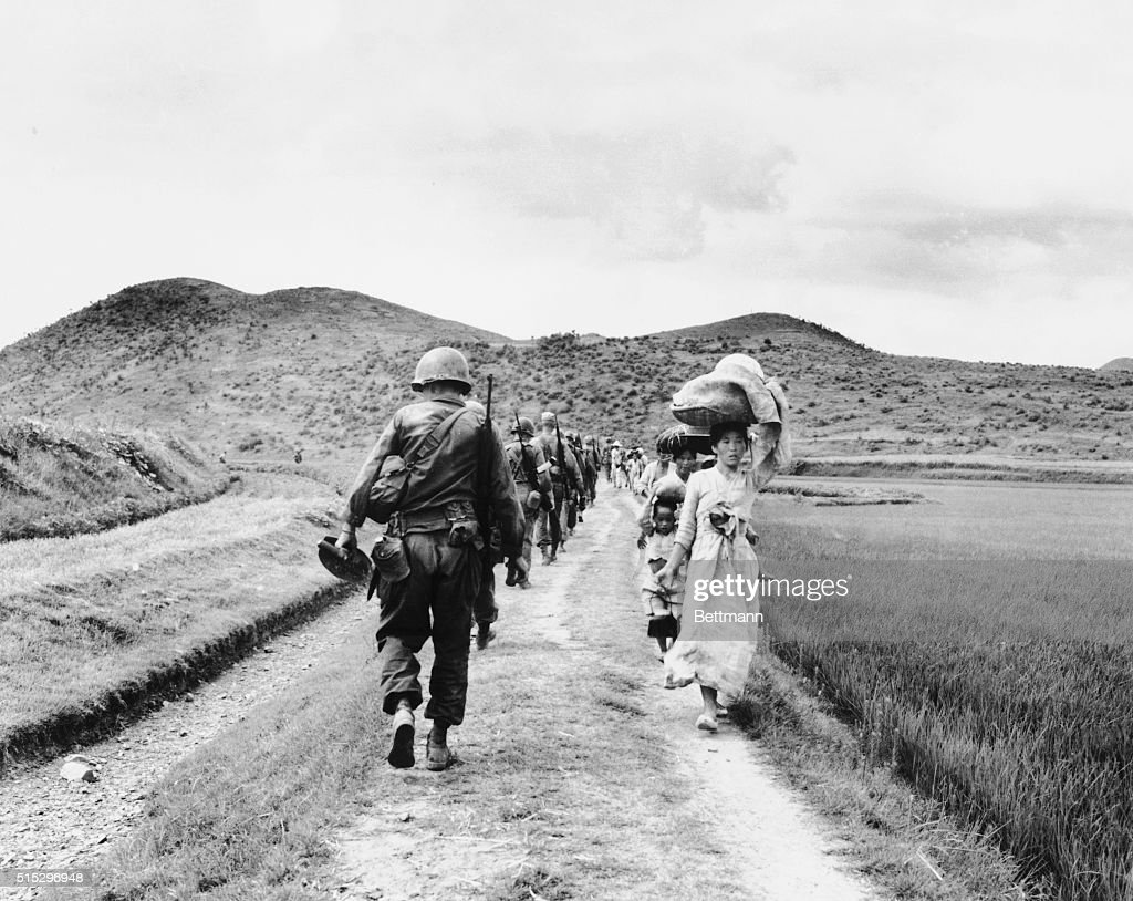As U.S. infantrymen march into the Naktong River region, they pass a line of fleeing refugees.