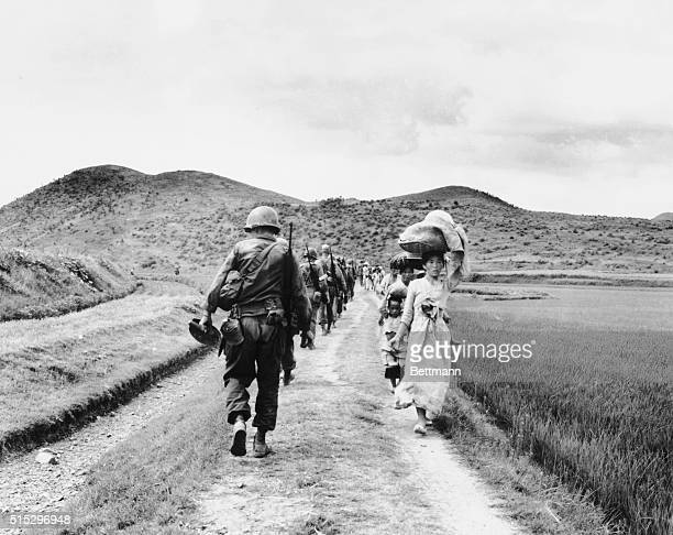 As US infantrymen march into the Naktong River region they pass a line of fleeing refugees