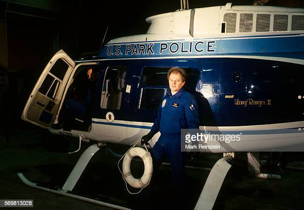 As US Park Police helicopter pilot Don Usher watches his cocrewman paramedic Gene Windsor stands on the copter's runner during a television interview...