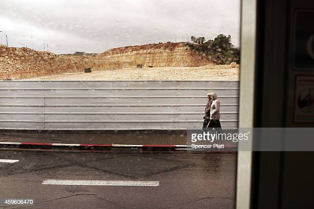 As viewed from a light rail tram people walk through a volatile East Jerusalem on November 26 2014 in Jerusalem Israel As of last month 15 of the...
