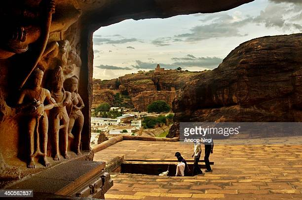 As we look out from Cave 3 to the outside you can see a sliver of the green lake and the township of Badami with a a perspective of the sculpted...