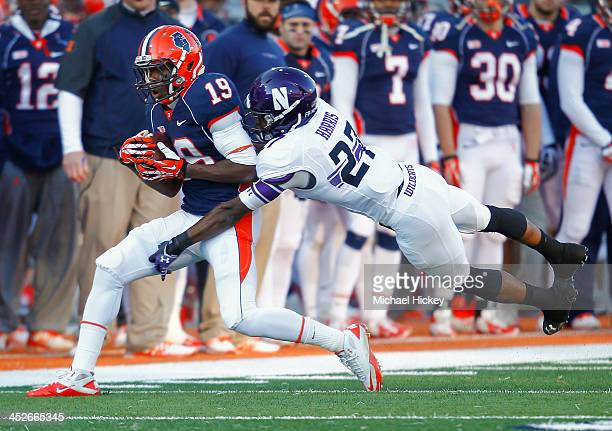 As wide receiver Justin Hardee of the Illinois Fighting Illini catches the ball cornerback Matthew Harris of the Northwestern Wildcats hits from...