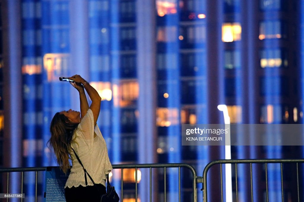 As woman takes picture as 'The Tribute in Light' illuminates the night sky, on September 10, 2017 in New York City. Commemorations are being held on the 16th anniversary of the 9/11 terror attacks, with President Donald Trump expected to speak at a ceremony for the 184 people killed at the Pentagon in Washington, DC. /