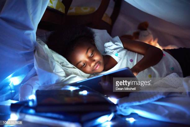 as you grow up, teddies are replaced with tablets - using digital tablet stock photos and pictures