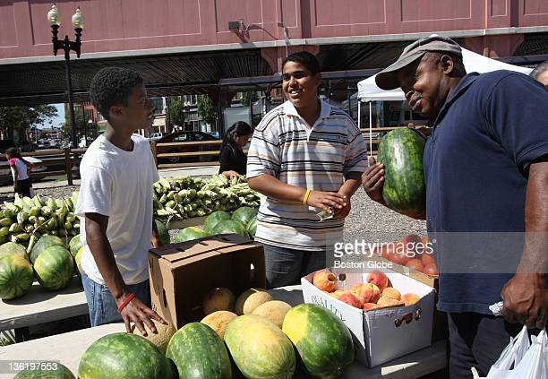 Asa Wigfall,13 and Raymond Tejeda both of Lynn, sell a watermelon to Jerry Handley of Lynn at the farmer's market in Central Square, Lynn.