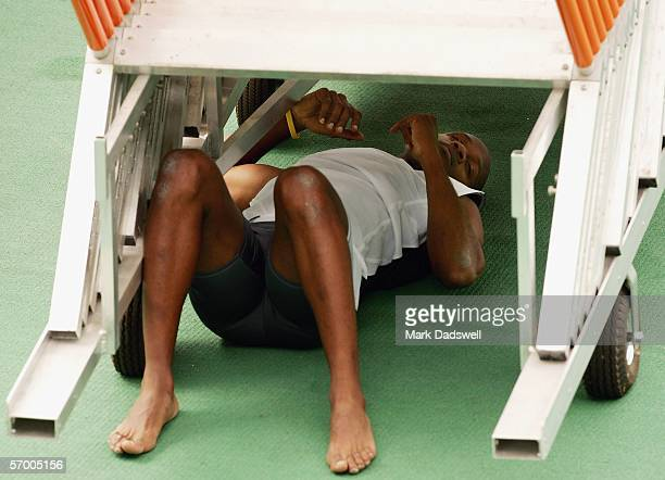 Asafa Powell of Jamaica lies exhausted under a rack of hurdles during a Commonwealth Games Athletics training session at Olympic Park March 6 2006 in...