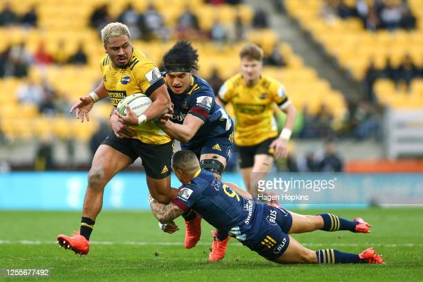 Asafo Aumua of the Hurricanes is tackled by Pari Pari Parkinson and Aaron Smith of the Highlanders during the round 5 Super Rugby Aotearoa match...