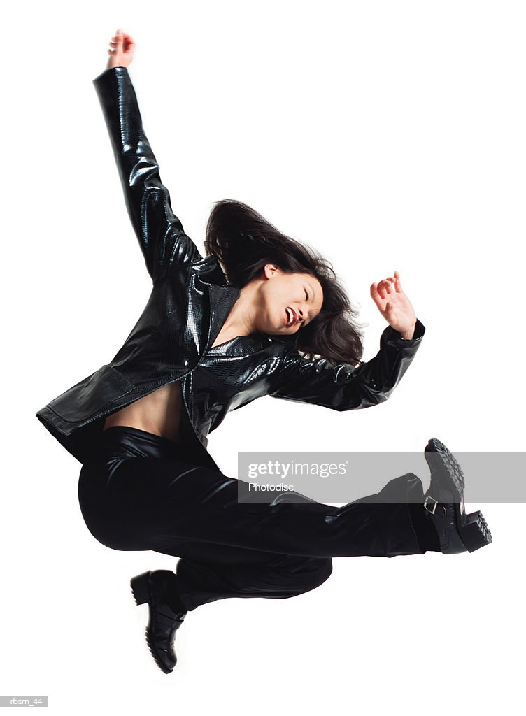asain woman in black leather pants and jacket jumping and kicking legs forward with arms swinging upward : Foto de stock