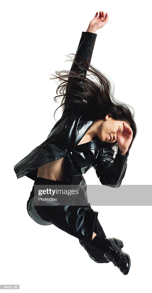 asain woman in black leather pants and jacket jumping with arms swinging in the air and legs swung forward : Foto de stock