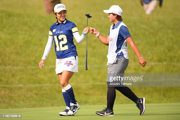 Asako Fujimoto of Japan celebrates the birdie with her caddie on the 10th green during the final round of Fujitsu Ladies at Tokyu Seven Hundred Club...