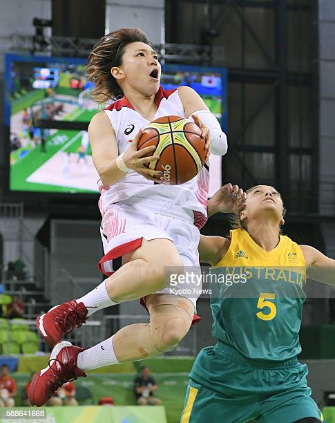Asami Yoshida of Japan drives past Australian point guard Leilani Mitchell for a shot during the first quarter of a women's basketball preliminary...
