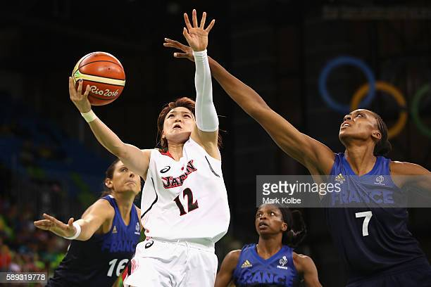 Asami Yoshida of Japan drives to the basket under pressure from Sandrine Gruda of France during the Women's preliminary round group A basketball...
