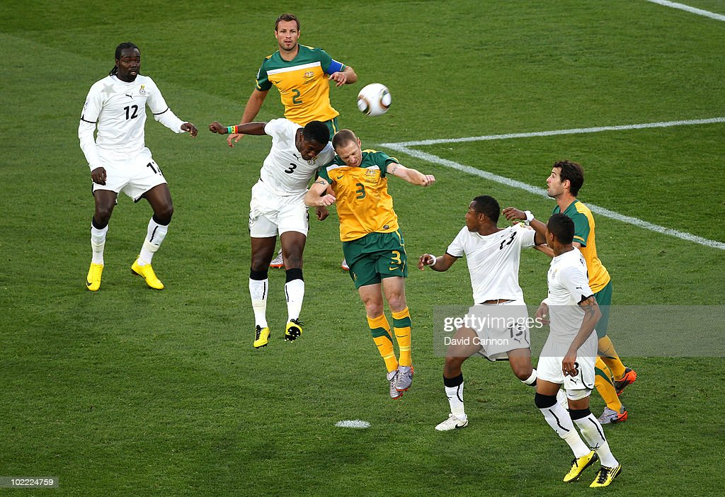 Asamoah Gyan of Ghana and Craig Moore of Australia jump for the ball during the 2010 FIFA World Cup South Africa Group D match between Ghana and Australia at the Royal Bafokeng Stadium on June 19, 2010 in Rustenburg, South Africa.