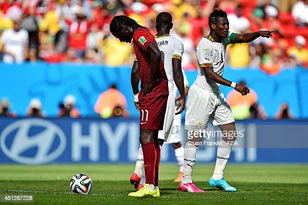 Asamoah Gyan of Ghana celebrates scoring his team's first goal while Eder of Portugal looks dejected during the 2014 FIFA World Cup Brazil Group G...