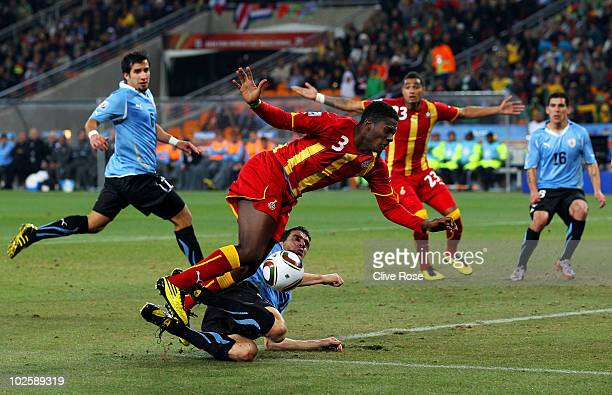 Asamoah Gyan of Ghana falls under the challenge from Andres Scotti of Uruguay during the 2010 FIFA World Cup South Africa Quarter Final match between...