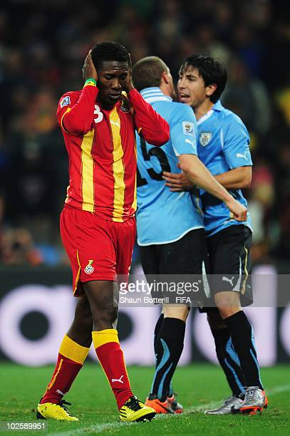 Asamoah Gyan of Ghana holds his head in shock after he hits a penalty kick onto the crossbar after Luis Suarez of Uruguay handles the ball off the...