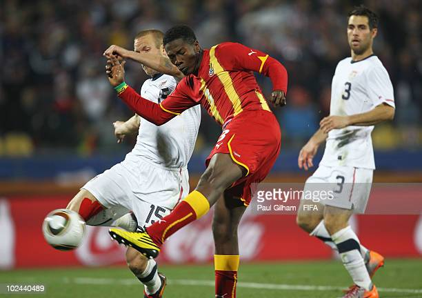 Asamoah Gyan of Ghana holds off Jay Demerit of the United States as he shoots and scores his side's second goal during the 2010 FIFA World Cup South...