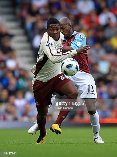 Asamoah Gyan of Sunderland beats Luis Boa Morte of West Ham United during the Barclays Premier League match between West Ham United and Sunderland at...