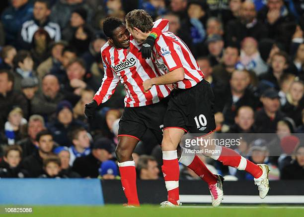 Asamoah Gyan of Sunderland celebrates with Jordan Henderson as he scores their second goal during the Barclays Premier League match between Chelsea...