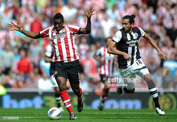 Asamoah Gyan of Sunderland in action with Jonas Gutierrez of Newcastle United during the Barclays Premier League match between Sunderland and...