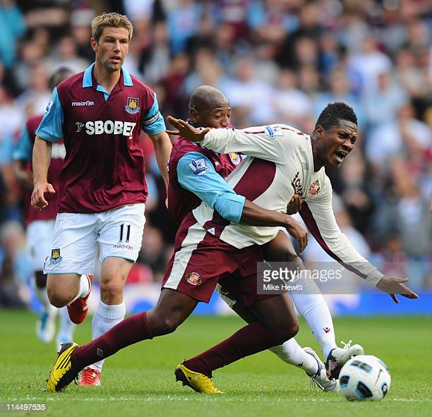Asamoah Gyan of Sunderland is challenged by Luis Boa Morte of West Ham during the Barclays Premier League match between West Ham United and...