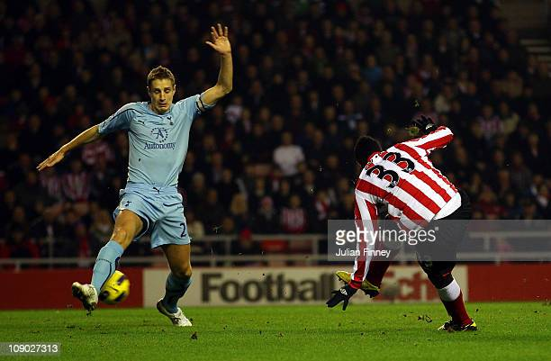 Asamoah Gyan of Sunderland scores the first goal as Michael Dawson of Spurs fails to block during the Barclays Premier League match between...
