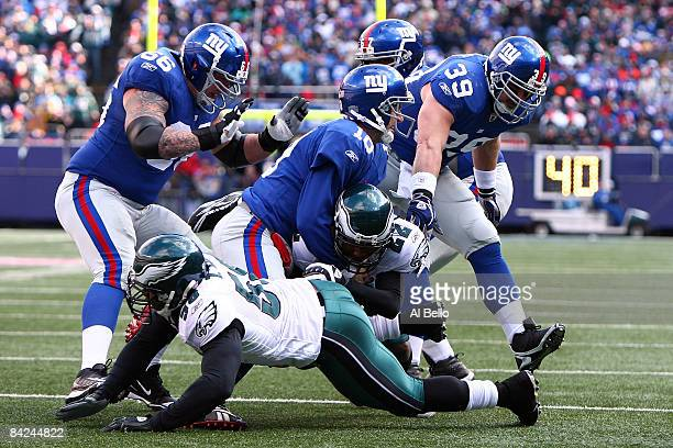 Asante Samuel of the Philadelphia Eagles is tackled by Eli Manning of the New York Giants after making an interception during the NFC Divisional...