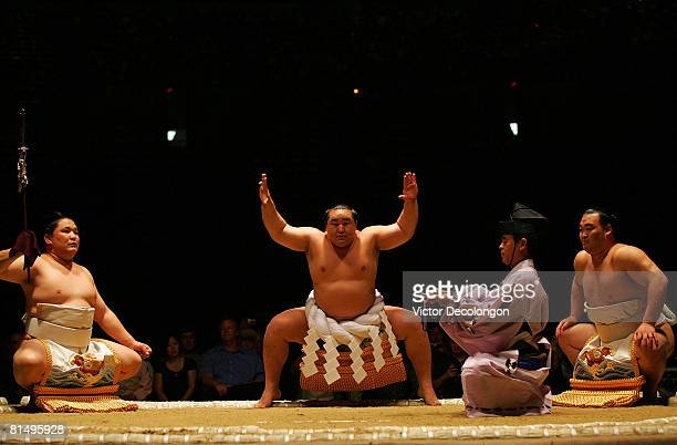 Asasashoryu performs the dohyoiri ceremony reserved for the yokozuna ranks of sumo as two makuuchi rikishi look on prior to the 2008 Grand Sumo...