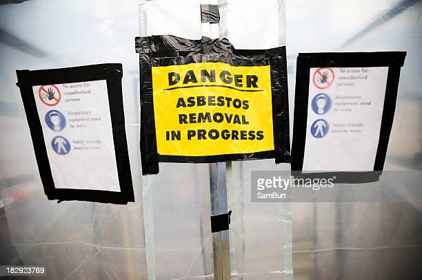 Asbestos removal signs on a plastic tent