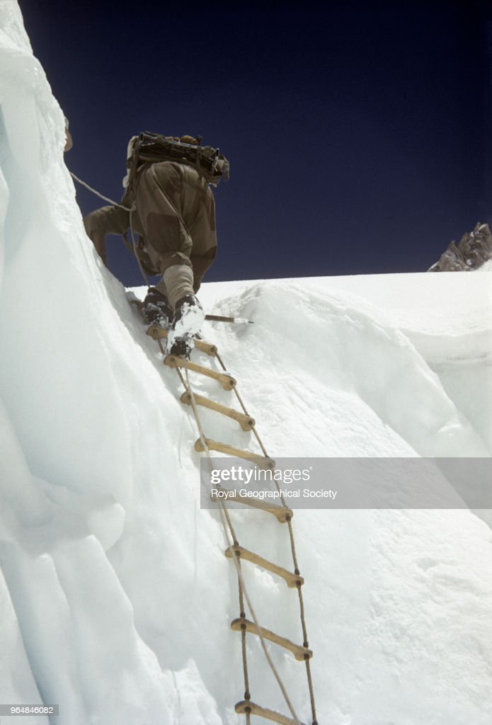 Ascending a rope ladder in the icefall, After passing through the dangers of the Khumbu Icefall and overcoming such hazards as 'The Nutcracker', 'The Atom Bomb Area' or 'MikeÆs Horror' expedition members arrived at the top of the Icefall to find the last and steepest ice wall. A rope ladder was firmly anchored in place to help pass this obstacle, Nepal, May 1953. Mount Everest Expedition 1953.
