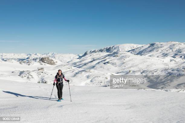 ascending a snowfield with snowshoes in the dachstein mountains, austria. - ski pants stock pictures, royalty-free photos & images