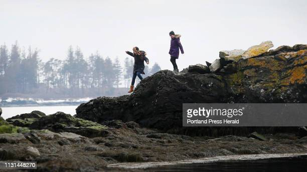Aschel Gregory of Cape Eliabeth left and Alicia Bergquist of Brunswick explore the rock outcroppings at Kettle Cove State Park on Thrusday March 14...