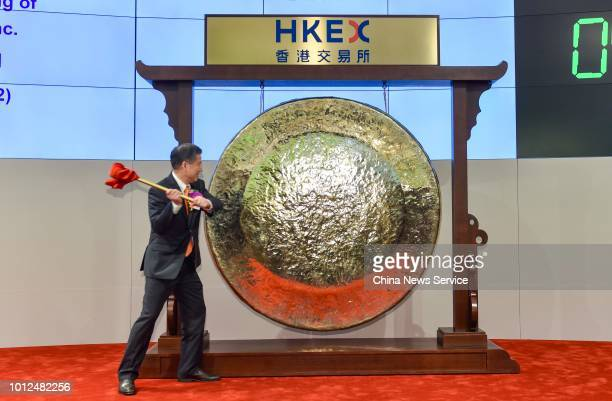 Ascletis Pharmaceutical chairman Wu Jinzi hits a gong during the company's listing ceremony at Hong Kong Stock Exchange on August 1, 2018 in Hong...