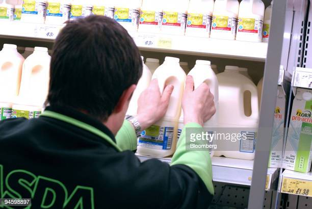 Asda employee replenishes milk shelves at a supermarket in Brighton UK Friday May 11 2007 Milk prices worldwide are rising at the fastest rate ever...