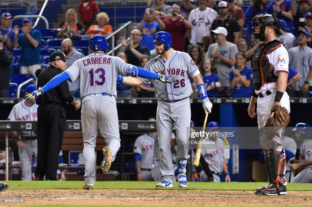 Asdrubal Cabrera #13 of the New York Mets celebrates with Kevin Plawecki #26 after hitting a home run in the eighth inning against the Miami Marlins at Marlins Park on April 10, 2018 in Miami, Florida.