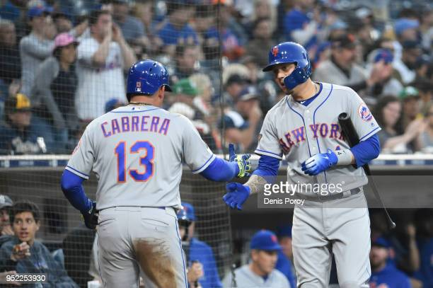 Asdrubal Cabrera of the New York Mets is congratulated by Wilmer Flores after scoring during the first inning of a baseball game against the San...