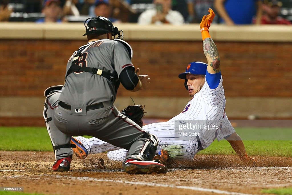 Asdrubal Cabrera #13 of the New York Mets is tagged out by Chris Iannetta #8 of the Arizona Diamondbacks trying to score on Yoenis Cespedes #52 single in th eseventh inning at Citi Field on August 21, 2017 in the Flushing neighborhood of the Queens borough of New York City.