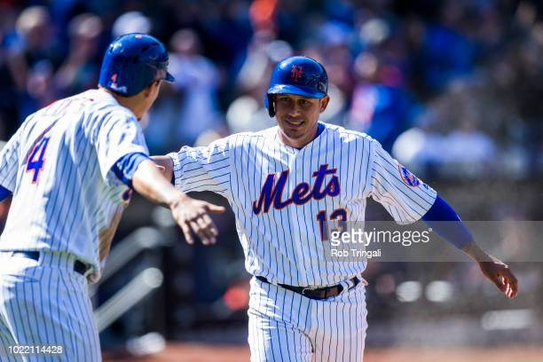 Asdrubal Cabrera of the New York Mets slaps hands with Wilmer Flores after scoring a run during the game against the Miami Marlins at Citi Field on...