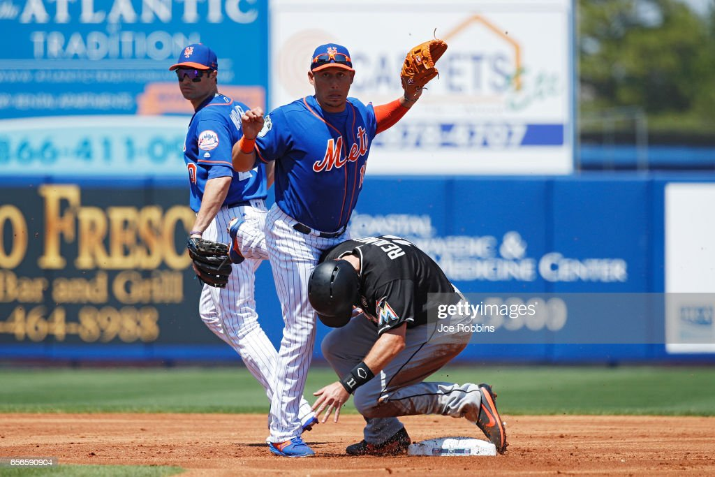Asdrubal Cabrera #13 of the New York Mets steps over J.T. Realmuto #11 of the Miami Marlins while trying to turn a double play in the first inning of a Grapefruit League spring training game at Tradition Field on March 22, 2017 in Port St. Lucie, Florida. The Marlins defeated the Mets 15-9.