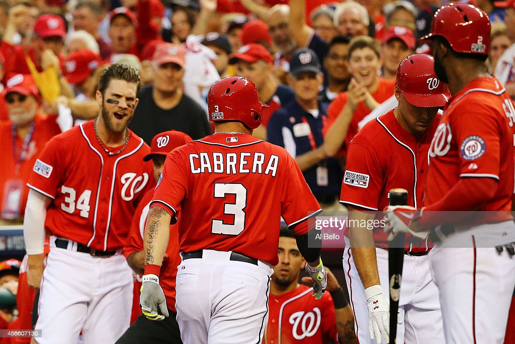 Asdrubal Cabrera #3 of the Washington Nationals celebrates his in the seventh inning home run with teammates during Game One of the National League Division Series against the San Francisco Giants at Nationals Park on October 3, 2014 in Washington, DC.