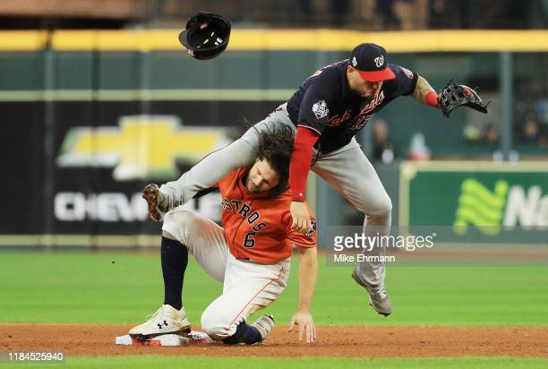 Asdrubal Cabrera of the Washington Nationals turns a double play against Jake Marisnick of the Houston Astros during the sixth inning in Game Seven...