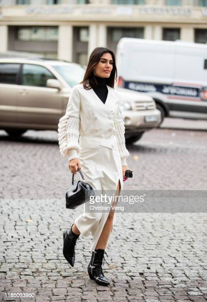 Asena Sarıbatur is seen wearing creme white coat, black laced boots, bag during day 3 of the Mercedes-Benz Tbilisi Fashion Week on November 02, 2019...