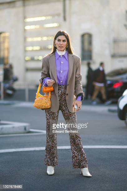 Asena Saribatur wears earrings, a purple leather shirt, a blazer jacket, an orange beaded bag, leopard prnt flared pants, white shoes, outside Prada,...